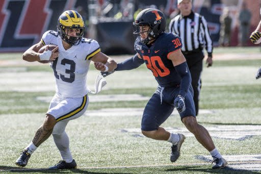 Michigan's Tru Wilson (13) runs the ball as Illinois' Sydney Brown (30) closes in during the first half of an NCAA college football game, Saturday, Oct. 12, 2019, in Champaign, Ill. (AP Photo/Holly Hart)