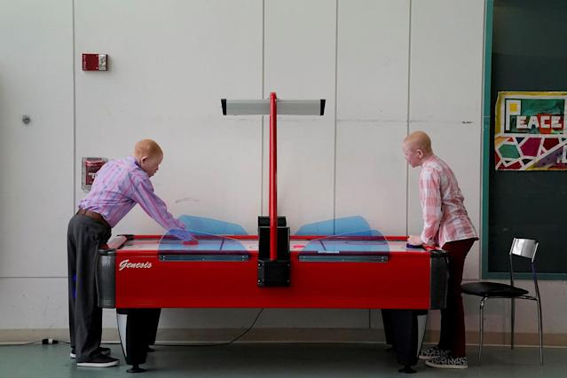 <p>Emmanuel Rutema, 15, and Pendo Noni 16, (R) play air hockey as they wait to have lunch after a prosthetic fitting at the Shriners Hospital in Philadelphia, Pa., May 30, 2017. Rutema and Noni are Tanzanians with albinism who had body parts chopped off in witchcraft-driven attacks. (Photo: Carlo Allegri/Reuters) </p>