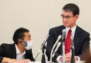 Japan's Vaccine Minister Taro Kono talks with his aide during a group interview in Tokyo