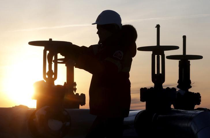 FILE PHOTO: A worker checks the valve of an oil pipe at Lukoil owned Imilorskoye oil field near Kogalym