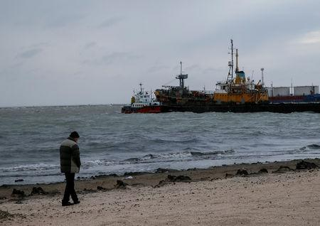 A man walks along a beach in front of the Azov Sea port of Berdyansk, Ukraine November 30, 2018. REUTERS/Gleb Garanich