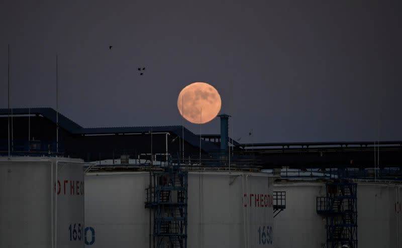 FILE PHOTO: The moon rises behind oil storage tanks in Omsk