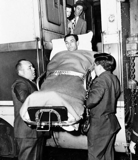 Golfer Ben Hogan of Fort Worth is ushered from train in which he made his trip back to Fort Worth.