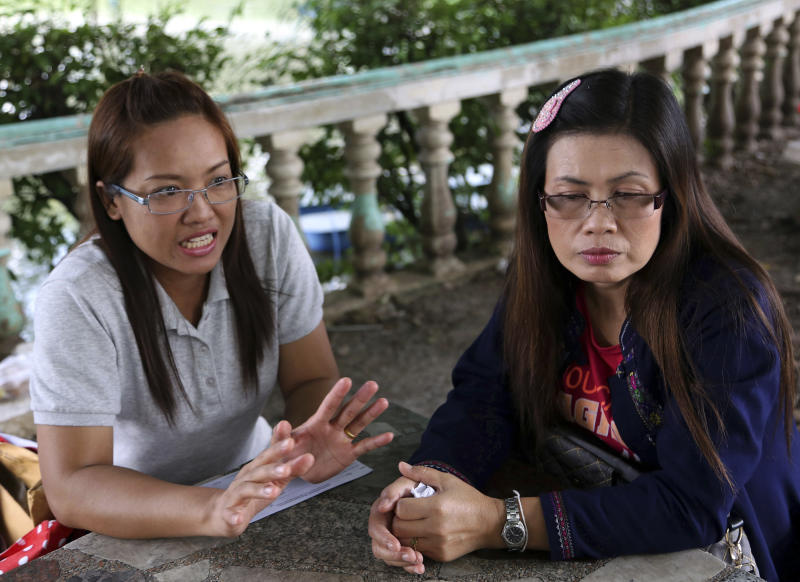 "In this photo taken Sept. 7, 2013, Jongkon Kongthin, 36, left, wife of Yuthapoom Martnok and Yuthapoom's sister Pinyo Ruaylarp, 42, talk during an interview outside a prison in Bangkok, Thailand. After having quarreled with his younger brother Yuthapoom, Thanawat Martnok told police that Yuthapoom had defamed King Bhumibol, an accusation that should be punished up to 15 years behind bars. Yuthapoom was indicted on charges of ""lese majeste"" - insulting the royal family. Denied bail on national security grounds, he has been jailed for a year in a Bangkok prison where he is anxiously awaiting the court's verdict Friday, Sept. 13, 2013. (AP Photo/Apichart Weerawong)"