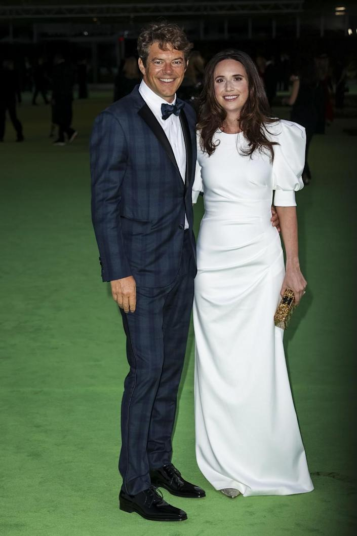 A man in a plaid, blue tuxedo and a woman in a white dress posing on a green carpet