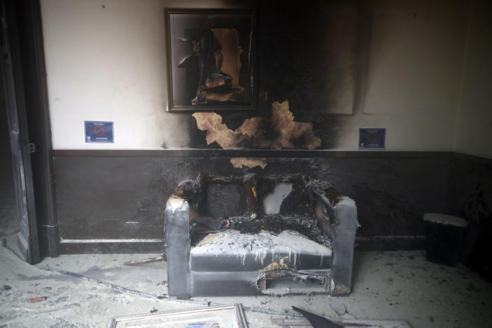 A couch and art work destroyed by fire are seen inside the Congress building after protesters set a part of building on fire, in Guatemala City, Saturday, Nov. 21, 2020. Hundreds of protesters were protesting in various parts of the country Saturday against Guatemalan President Alejandro Giammattei and members of Congress for the approval of the 2021 budget that reduced funds for education, health and the fight for human rights. (AP Photo/Moises Castillo)