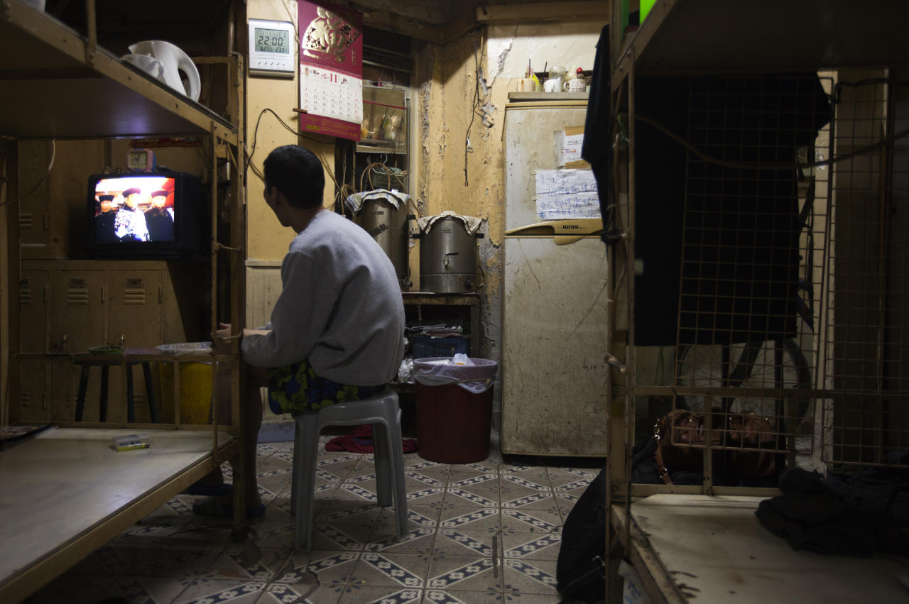 A resident watches TV in a common area in front of his bed which he rents for $167 as his home in Hong Kong November 1, 2012. REUTERS/Tyrone Siu