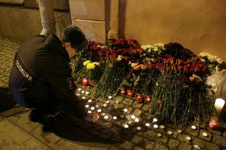 A police officer leaves a candle during a memorial service for victims of a blast in St. Petersburg metro, outside Tekhnologicheskiy institut metro station in St. Petersburg, Russia April 3, 2017. REUTERS/Anton Vaganov