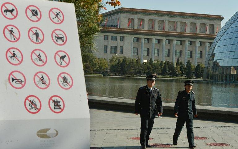 Chinese security officers patrol in a park beside the Great Hall of the People in Beijing on November 12, 2012