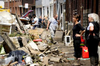 Residents put unwanted personal belongings in a pile on the street after flooding in Drolenvol, Belgium, Saturday, July 17, 2021. Residents in several provinces were cleaning up after severe flooding in Germany and Belgium turned streams and streets into raging torrents that swept away cars and caused houses to collapse. (AP Photo/Virginia Mayo)