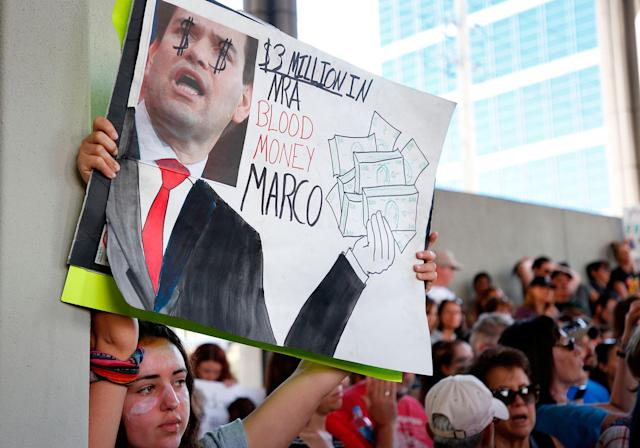 <p>Protesters hold signs at a rally for gun control at the Broward County Federal Courthouse in Fort Lauderdale, Fla., on Feb. 17, 2018. (Photo: Rhona Wise/AFP/Getty Images) </p>