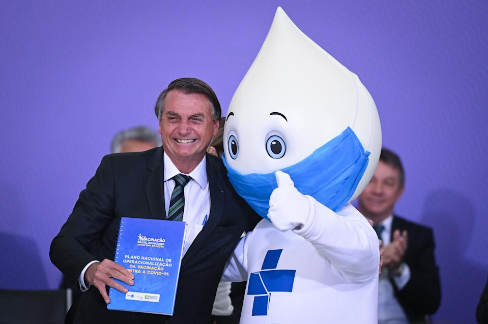 Brazil's president Jair Bolsonaro reacts next to ''Ze Gotinha'', vaccination campaign mascot, during the launching ceremony of the National Vaccination Operationalization Plan against COVID-19 at Planalto Palace in Brasilia, Brazil, on Wednesday, Dec. 16, 2020. (Photo by Andre Borges/NurPhoto via Getty Images)