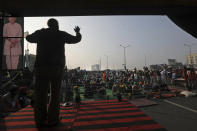 An Indian farmer addresses fellow farmers blocking a highway in protest against new farm laws at the Delhi-Uttar Pradesh state border, on the outskirts of New Delhi, India, Wednesday, Dec. 30, 2020. Protesting farmers fear the government will stop buying grain at minimum guaranteed prices and corporations will then push down prices. The government says the three laws approved by Parliament in September will enable farmers to market their produce and boost production through private investment. (AP Photo/Manish Swarup)