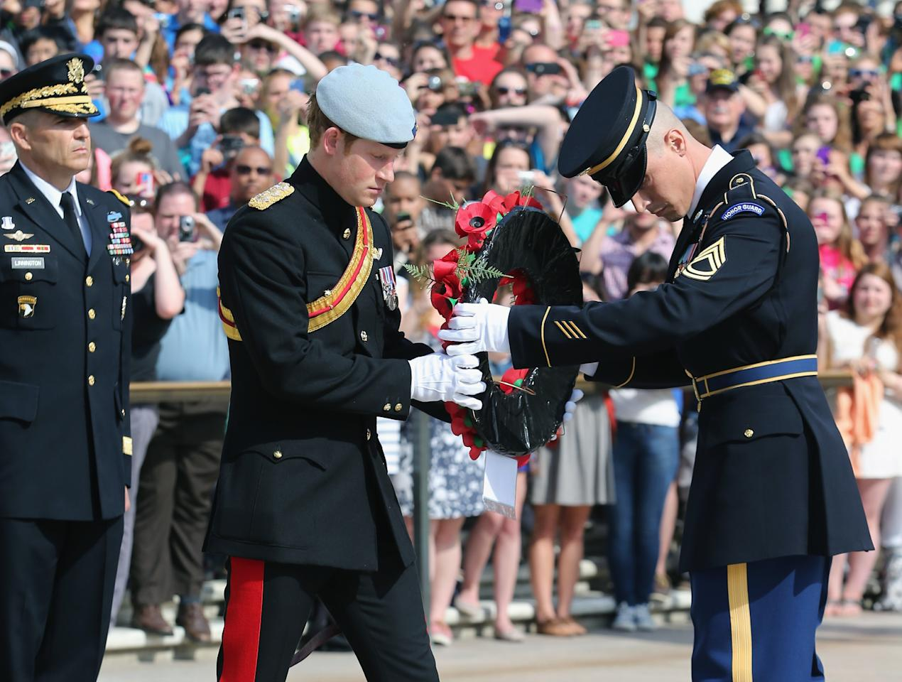 ARLINGTON, VA - MAY 10:  HRH Prince Harry wearing his No. 1 ceremonial uniform of The Blues and Royals along with an honor guard lays a wreath as he pays his respects to the victims of the Afghanistan conflict and the tomb of the unknown soldieras Major General Michael Linnington looks on during the second day of his visit to the United States at Arlington National Cemetery on May 10, 2013 in Arlington, Virginia. HRH will be undertaking engagements on behalf of charities with which the Prince is closely associated on behalf also of HM Government, with a central theme of supporting injured service personnel from the UK and US forces.  (Photo by Chris Jackson/Getty Images)