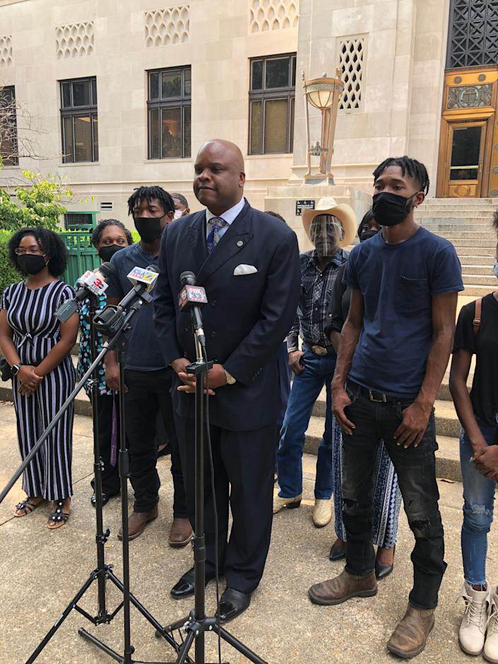 Attorney James Carter, surrounded by the family of Tommie McGlothen Jr., takes questions during a press conference on Friday. Four Shreveport police officers have been indicted on charges of negligent homicide and malfeasance.