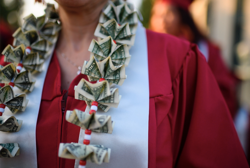 """A graduating student wears a money lei, a necklace made of US dollar bills, at the Pasadena City College graduation ceremony, June 14, 2019, in Pasadena, California."" (Photo: ROBYN BECK/AFP/Getty Images)"