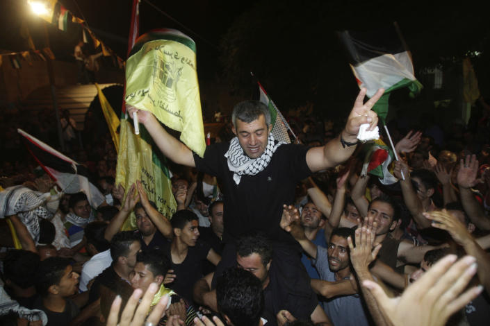 Palestinians celebrate the release of Mohammed Sawalha, center, in Azmout village near Nablus in the West Bank, Wednesday, Aug. 14, 2013. Israel released 26 Palestinian inmates, including many convicted in grisly killings, on the eve of long-stalled Mideast peace talks, angering families of those slain by the prisoners, who were welcomed as heroes in the West Bank and Gaza. (AP Photo / Nasser Ishtayeh)