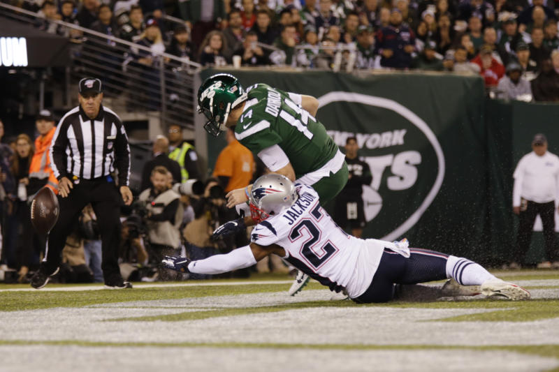 New England Patriots' J.C. Jackson (27) and New York Jets' Sam Darnold (14) fights for control of the ball in the end zone after it was snapped over the head of Darnold during the second half of an NFL football game Monday, Oct. 21, 2019, in East Rutherford, N.J. The Patriots scored a safety on the play. (AP Photo/Adam Hunger)