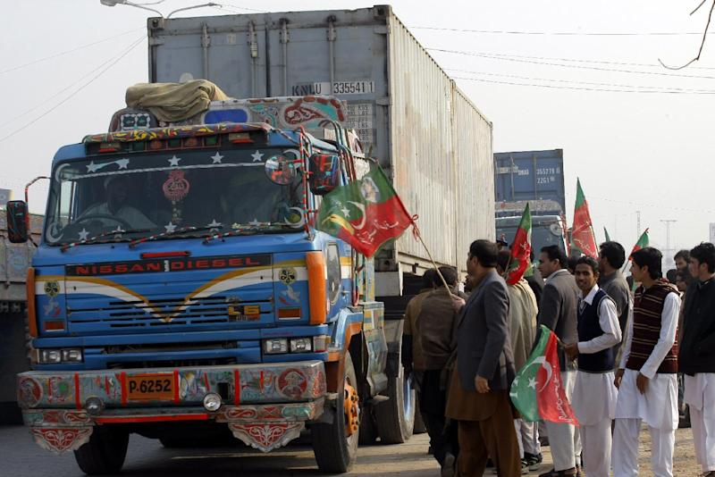 In this photo taken on Monday, Dec. 16, 2013, workers of Pakistan Tehreek-e-Insaf check private containers on their way to neighboring Afghanistan in Peshawar, Pakistan. Tehreek-e-Insaf, headed by cricketer-turned politician Imran Khan, has stopped movement of NATO containers to Afghanistan which has frustrated the U.S. officials. (AP Photo/Mohammad Sajjad)
