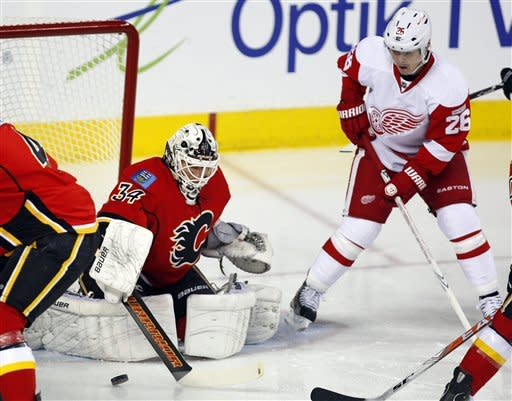 Detroit Red Wings' Jiri Hudler (26) from the Czech Republic, looks on as Calgary Flames goalie Miikka Kiprusoff, from Finland, makes a save during the first period of an NHL hockey game in Calgary, Alberta, Thursday, Dec. 22, 2011. (AP Photo/The Canadian Press, Jeff McIntosh)