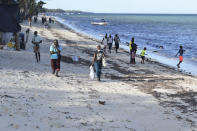People walk along the Jomo Kenyatta Public Beach in Mombasa, Kenya, Friday April 2, 2021. Most of the holiday makers were turned away by security officers saying that the government had closed all public places including the beach, due to the COVID-19 pandemic. (AP Photo/Gideon Maundu)