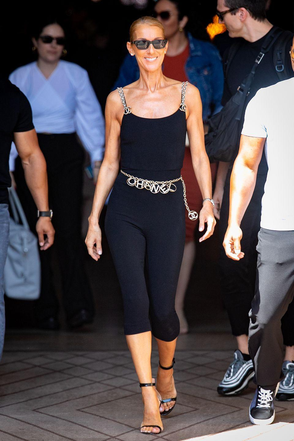 <p>Celine certainly does athleisure better than we do. For this monochrome look, she paired a catsuit with Chanel bling, a Chanel chain belt, and black ankle-strap heels. </p>