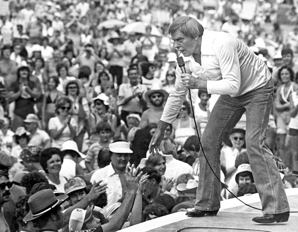 """FILE - In this July 16, 1977 file photo, Singer Tom T. Hall leans to the edge of the stage at the Jamboree in the Hills to meet the people near St. Clairsville, Ohio. Singer-songwriter Tom T. Hall, who composed """"Harper Valley P.T.A."""" and sang about life's simple joys as country music's consummate blue collar bard, has died. He was 85. His son, Dean Hall, confirmed the musician's death Friday, Aug. 20, 2021 at his home in Franklin, Tennessee.(AP Photo/File)"""