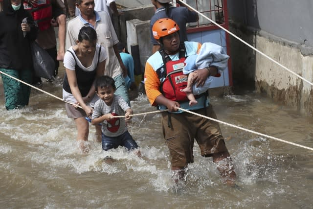 A rescuer evacuates a baby in a flooded neighbourhood in Tanggerang outside Jakarta, Indonesia