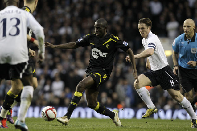 Bolton Wanderers' Fabrice Muamba, center, controls the ball beside Tottenham Hotspur's Scott Parker, right, during the English FA Cup quarterfinal soccer match at White Hart Lane stadium in London, Saturday, March 17, 2012. Bolton midfielder Fabrice Muamba has been carried off the field at Tottenham after medics appeared to be trying to resuscitate him during an FA Cup quarterfinal that was abandoned. Muamba went to the ground in the 41st minute with no players around him and the game was immediately stopped. (AP Photo/Matt Dunham)