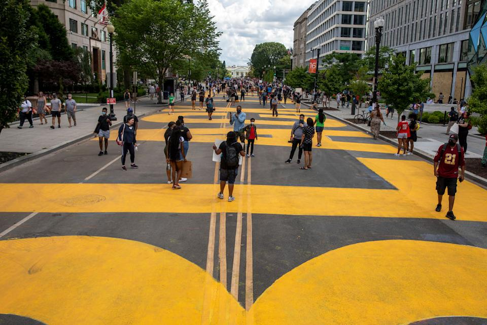 """People walk down 16th street after volunteers, with permission from the city, painted """"Black Lives Matter"""" on the street near the White House. Source: Getty Images"""