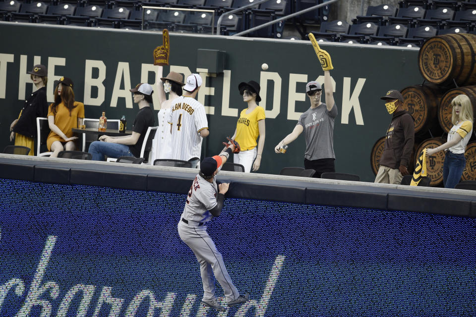 Houston Astros right fielder Josh Reddick jumps up onto the outfield wall while trying to catch a grand slam by San Diego Padres' Jake Cronenworth during the second inning of a baseball game in San Diego, Saturday, Aug. 22, 2020. (AP Photo/Kelvin Kuo)