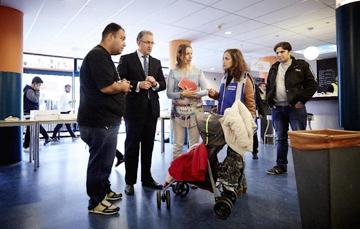The Netherlands has agreed to take over 7,000 refugees as part of the EU's migrant quota proposal, as Rotterdam mayor Ahmed Aboutaleb (2nd left) talks to asylum-seekers at the Erasmus University, on September 18, 2015 (AFP Photo/Martijn Beekman)