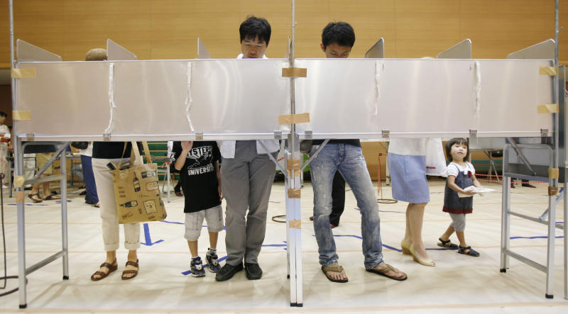 Voters select candidates before casting their ballots in Japan's upper house parliamentary elections at a polling station in Tokyo, Sunday, July 21, 2013. Japanese voters went to the polls Sunday in an upper house of parliament election expected to give Prime Minister Shinzo Abe's ruling coalition a strong mandate as he pushes ahead with economic reforms and his conservative political agenda. (AP Photo/Koji Sasahara)