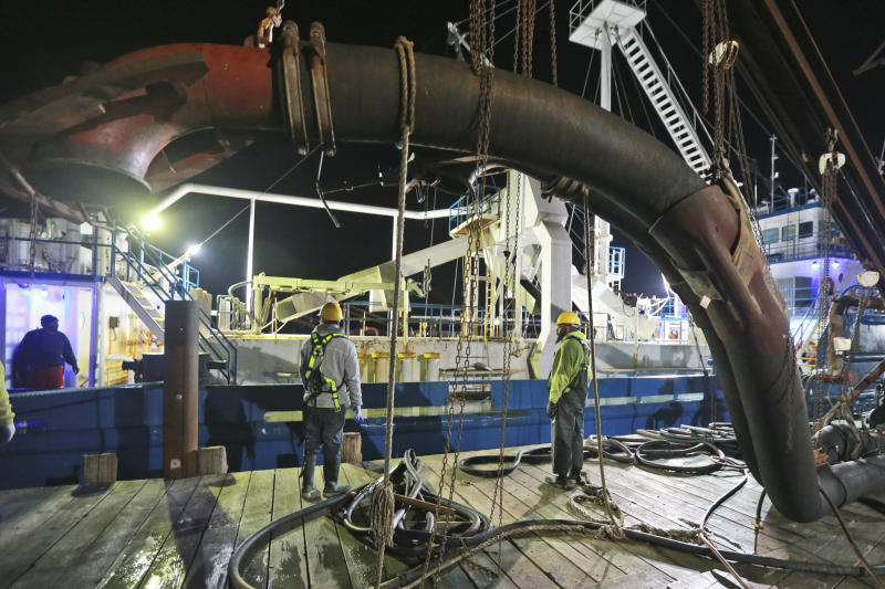 In this Tuesday, Nov. 26, 2019 photo, Workers prepare to attach suction hose to the menhaden fishing boat Windmill Point at Omega Protein's menhaden processing plant on Cockrell's Creek in Reedville, Va. The Trump Administration is threatening to effectively ban a company that makes fish oil pills from fishing in the Chesapeake Bay over mounting concerns from regulators, governors and environmental groups about overfishing. Earlier this year, the company Omega Protein exceeded harvest limits in the bay by more than 30% on a bony and oily fish called Atlantic menhaden.  (AP Photo/Steve Helber)