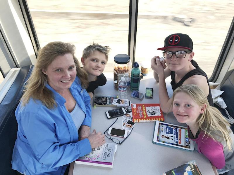 In this photo taken Saturday, Jan. 28, 2017, Pam Buresh, 54, of Oregon sits with her three children: Tyson, Ethan and Riley, from left. They were going to Disneyland. AP Tampa correspondent Tamara Lush spent 15 days traveling via train across the U.S. as part of Amtrak's residency program, designed for creative professionals to spend time writing on the rails. She spoke with dozens of people _ fellow travelers, friends and family waiting for loved one at stations, train workers _ and filed occasional dispatches for the Tales on a Train project. (AP Photo/Tamara Lush)