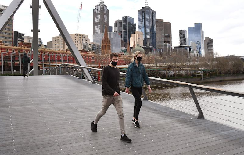 A couple walks on a footbridge over the Yarra River in the Southbank district of Melbourne on August 12, 2020, during a strict stage four lockdown of the city due to a COVID-19 coronavirus outbreak. - Australia's worst-hit state of Victoria appears to be curbing a virus outbreak after a week of tougher restrictions, authorities said on August 12, with new cases falling in recent days even as fatalities topped records. (Photo by William WEST / AFP) (Photo by WILLIAM WEST/AFP via Getty Images)