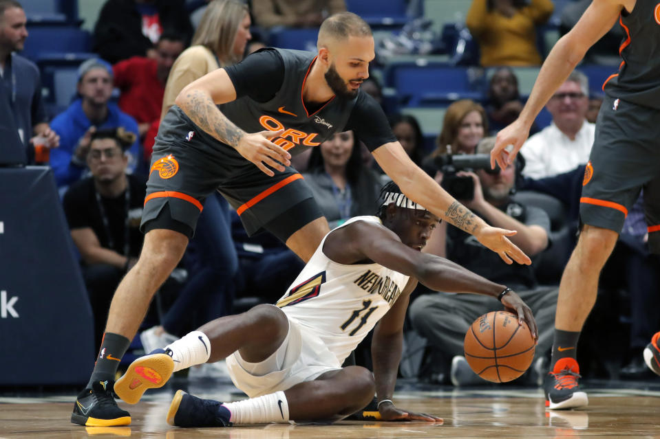 New Orleans Pelicans guard Jrue Holiday (11) battles for a loose ball against Orlando Magic guard Evan Fournier (10) in the first half of an NBA basketball game in New Orleans, Sunday, Dec. 15, 2019. (AP Photo/Gerald Herbert)
