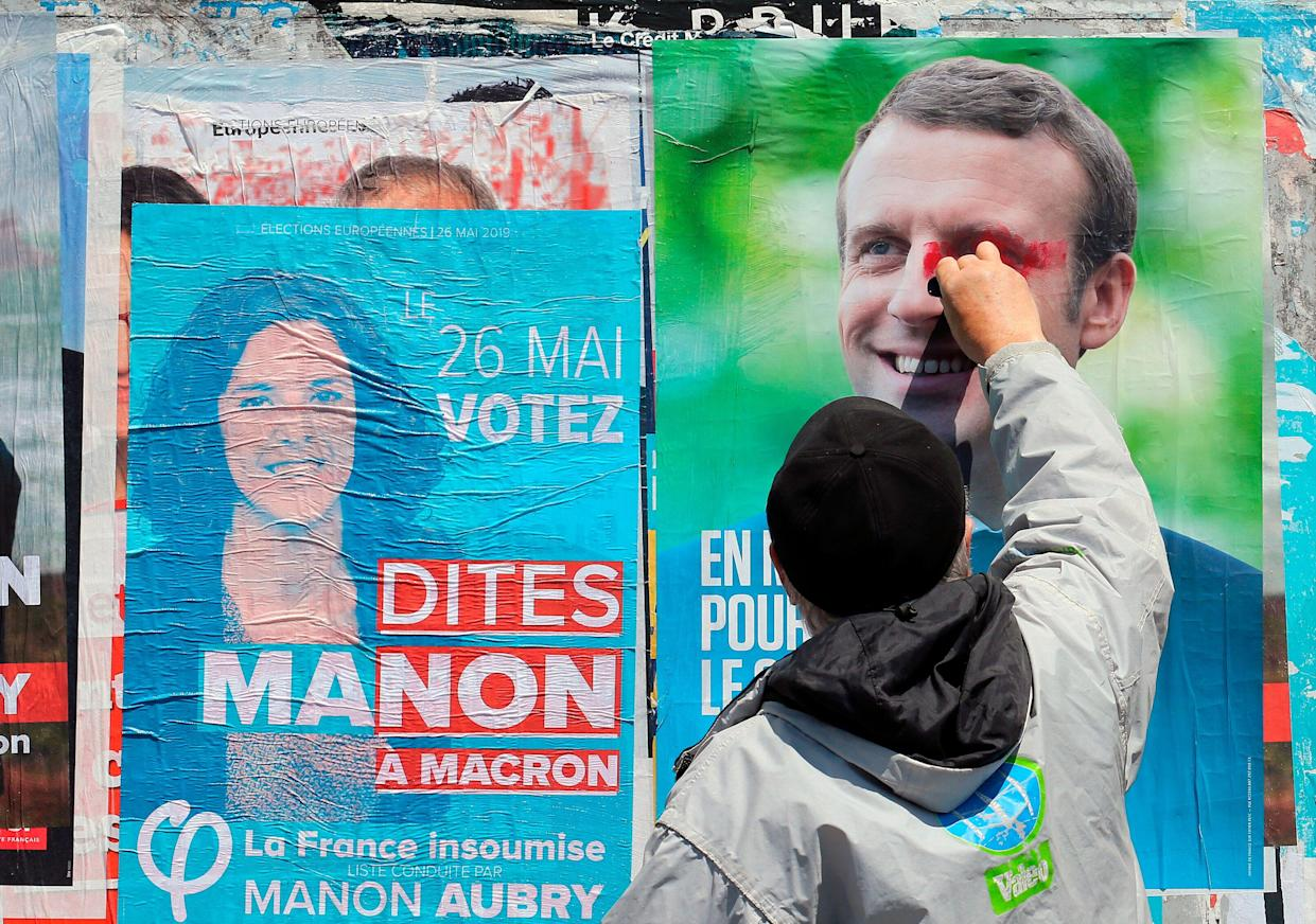 A supporter of French candidate Manon Aubry scribbles on a campaign poster of French President Emmanuel Macron, May 21. (Photo: Bob Edme/AP)