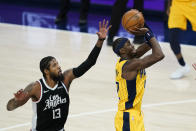 Indiana Pacers' Caris LeVert (22) shoots against Los Angeles Clippers' Paul George (13) during the second half of an NBA basketball game, Tuesday, April 13, 2021, in Indianapolis. (AP Photo/Darron Cummings)