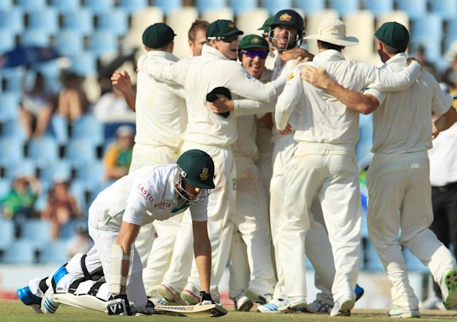 South Africa's batsman, Morne Morkel, bottom, kneels on the ground after a run out as Australia's players celebrate their winning wicket on the fourth day of their cricket test match at Centurion Park in Pretoria, South Africa, Saturday, Feb. 15, 2014. Australia beat South Africa by 281 runs. (AP Photo/ Themba Hadebe)