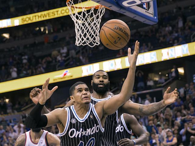 Orlando Magic's Tobias Harris (12) and Kyle O'Quinn, right, reach for a rebound after a missed New York Knicks shot in overtime of an NBA basketball game in Orlando, Fla., Friday, Feb. 21, 2014. The Magic won 129-121 in two overtimes. (AP Photo/Willie J. Allen Jr.)