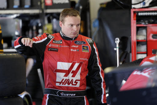 Cole Custer waits in his garage as crew members work on his car during a NASCAR auto race practice at Daytona International Speedway, Saturday, Feb. 8, 2020, in Daytona Beach, Fla. (AP Photo/Terry Renna)