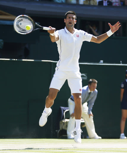 Novak Djokovic of Serbia jumps up to play a return toGrigor Dimitrov of Bulgaria during their men's singles semifinal match at the All England Lawn Tennis Championships in Wimbledon, London, Friday, July 4, 2014. (AP Photo/Pavel Golovkin)