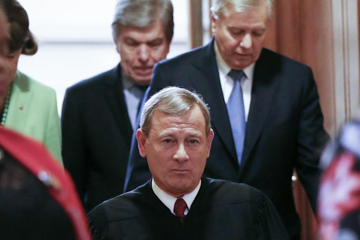Supreme Court Chief Justice John Roberts (C) departs the Senate chamber along with Sen. Lindsey Graham (R-SC) (TOP R) and Sen. Roy Blunt (R-MO) after the Senate impeachment trial of U.S. President Donald Trump concluded on February 5, 2020 in Washington, DC. (Mario Tama/Getty Images)