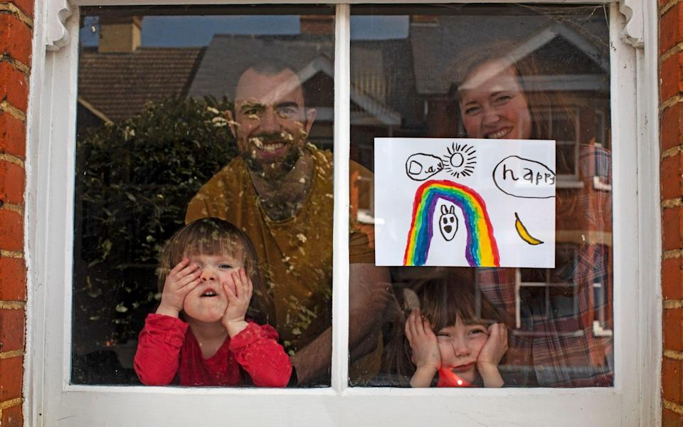 Amelie and her sister, Camille, look out from their front window in the COVID-19 coronavirus lockdown along with their parents, Victoria and Damian Kerr, in Berkhamsted, England -Lockdown saved no lives and may have cost them, Nobel Prize winner believes - AP