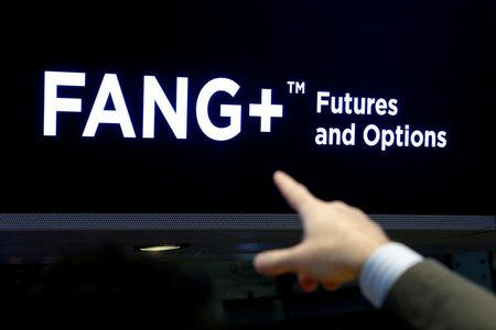 FILE PHOTO: A trader points to a screen that displays FANG+ group of highly-traded technology and tech-enabled companies on the floor of the NYSE in New York