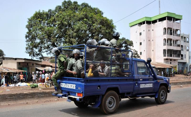 Officers patrol in a gendarmerie's vehicle in Conakry on May 7, 2015
