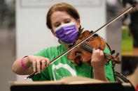 """Violinist Katie Kresek, who is also the concertmaster and co-orchestrator for the Tony-nominated Broadway musical """"Moulin Rouge,"""" plays for people waiting out their post-vaccination observation period after receiving a COVID-19 vaccine at the Jacob K. Javits Convention Center, Thursday, March 18, 2021, in New York. (AP Photo/Kathy Willens)"""