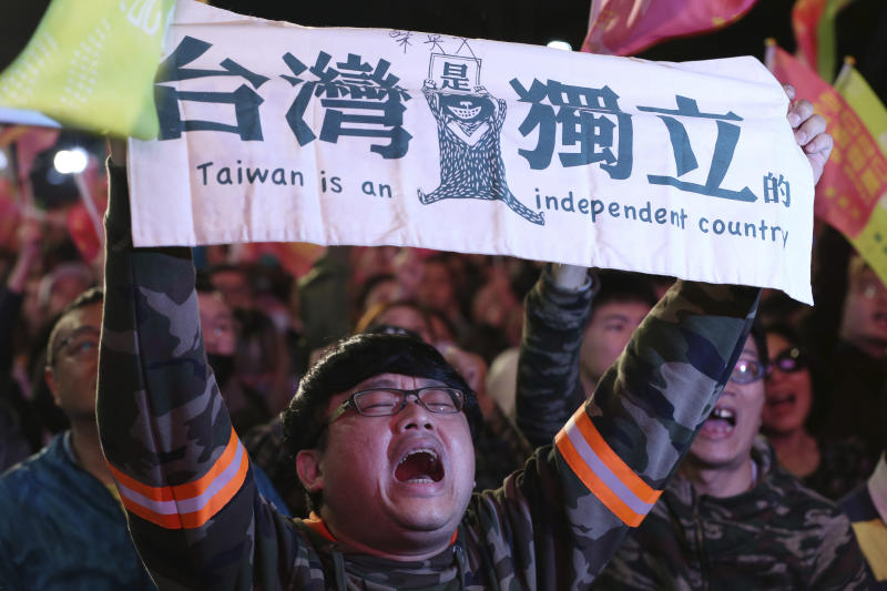 "In this Jan. 11, 2020, photo, a supporter of Taiwan's presidential election candidate, Taiwan president Tsai Ing-wen cheers for her victory and holds a slogan reading ""Taiwan Is An Independent Country"" in Taipei, Taiwan, Saturday, Jan. 11, 2020. (AP Photo/Chiang Ying-yin, File)"