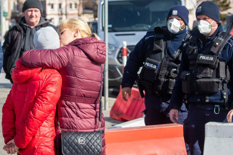 Police officers wearing face masks watch a woman kissing a child for goodbye as returning Poles cross the Polish-German border from the eastern German town of Frankfurt (Oder) to Slubice on March 16, 2020, as measures are taken to slow down the spread of the novel coronavirus. - Polish Prime Minister Mateusz Morawiecki said Poland's borders would be closed to foreigners for 10 days, but that the government might prolong the shutdown. Two weeks of quarantine will also be imposed on people returning from abroad. (Photo by Odd ANDERSEN / AFP) (Photo by ODD ANDERSEN/AFP via Getty Images)